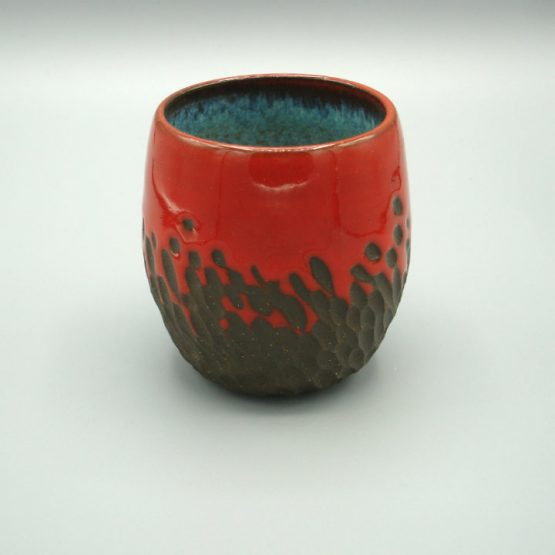 Red ceramic wine goblet with dark clay carving